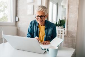 Hymyilevä nainen tietokoneella