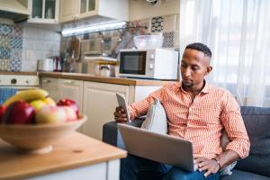 Mies katselee matkapuhelintaan ja hänellä sylissään tietokone.