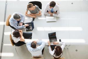 Johtaja esittelee työntekijöille asioita tietokoneeltaan.