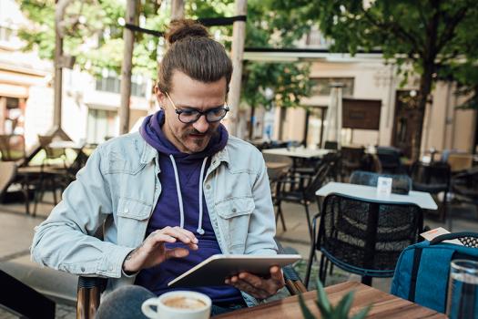 Mies istuu kahvilassa ja selaa iPadia.