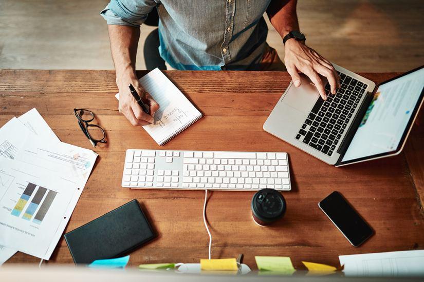 Mies tekee muistiinpanoja tietokoneella
