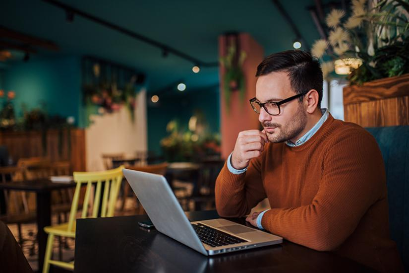 Mies katsoo vakavana tietokonetta.
